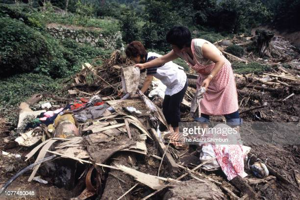 Residents pick up stuffs at a place their house used to stand after a landslide is seen triggered by Typhoon Bess hits across Japan on August 4, 1982...