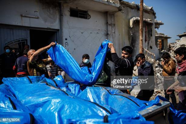 Residents pile up body bags in the back of a pick up truck after recovering it from the rubble where there were reported coalition air strikes in the...