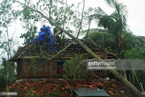 Residents place a tarpaulin over the damage roof of a house following the landfall of cyclone Amphan in Khejuri area of Midnapore West Bengal on May...