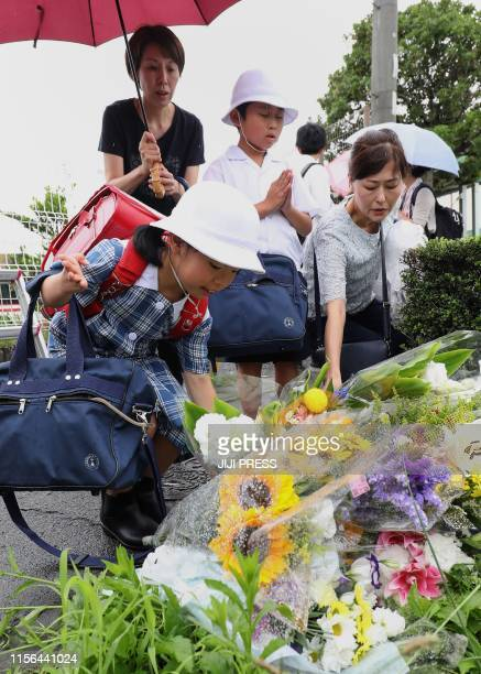 Residents place flowers for victims of a fire which hit the Kyoto Animation studio building the day before killing 33 people in Kyoto on July 19 2019...