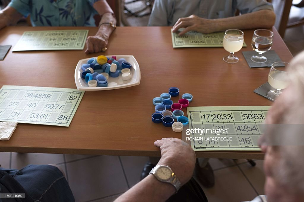 Residents play a game of Lotto with water bottle caps at a