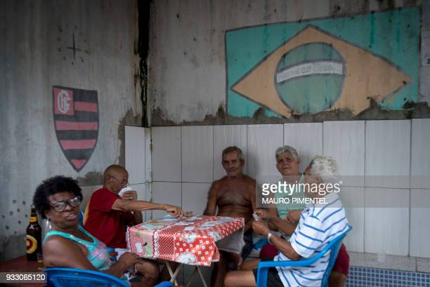 Residents play cards in a bar at Vila Kennedy favela in Rio de Janeiro Brazil on March 17 2018 The chaos in the favelas continues despite President...