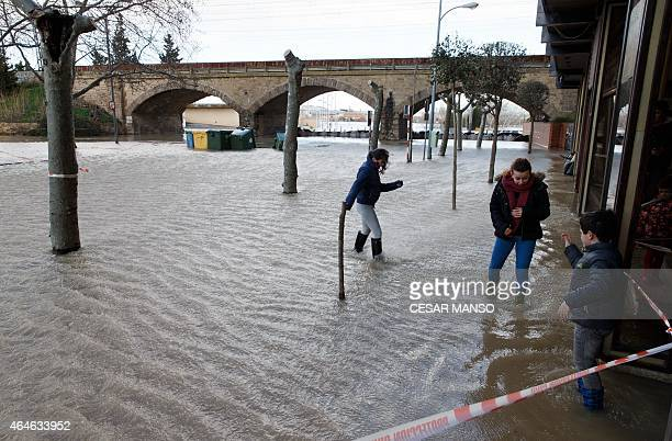 Residents play on a flooded street after the river Ebro in Tudela broke its banks following heavy rainfall on February 27 2015 AFP PHOTO / CESAR MANSO