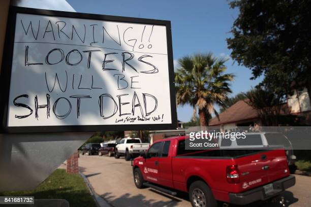 Residents post a warning to looters as they recover from damage to their homes after torrential rains caused widespread flooding during Hurricane and...