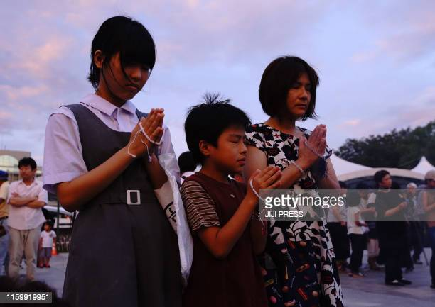 Residents pray to mourn victims in the early morning prior to the 74th anniversary of memorial service for atomic bomb victims at the Peace Memorial...