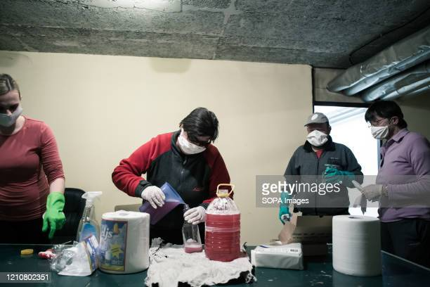 Residents prepare disinfectant solutions while wearing protective masks as a preventive measure during the Coronavirus lockdown crisis. Slovenia has...