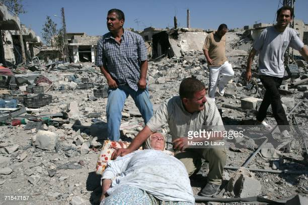 Residents prepare to carry on a makeshift stretcher a woman who was trapped in the rubble of her house as they flee the city July 31 2006 in Bint...