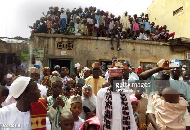 Residents prepare to pay their respects to an unseen Emir of Kano Muhammadu Sanusi II as he departs on horseback from the Eid prayer ground in Kano...