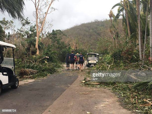 Residents procced to clear roads of fallen tree on the Hamilton Island after strong Cyclone Debbie hit the Whitsundays Islands in Queensland on March...