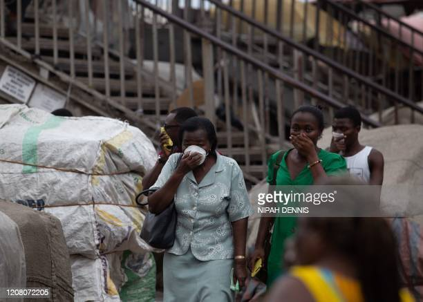 Residents protect their faces with masks and other items as a preventive measure against COVID-19 Coronavirus as city worker disinfects a market n...