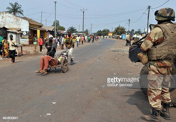 Residents push a man wounded by a machete during looting on January 24 2014 at P12 district in the north of Bangui Central African Republic's new...