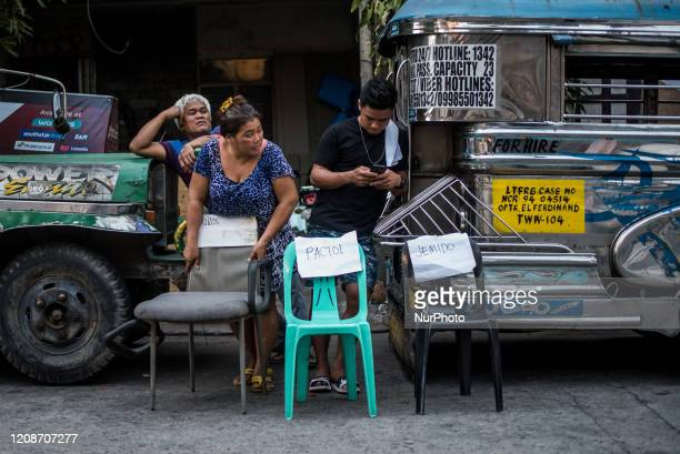 Residents put up chairs bearing their names along the street to serve as drop off points for relief goods in Quezon City Philippines on March 30 2020...