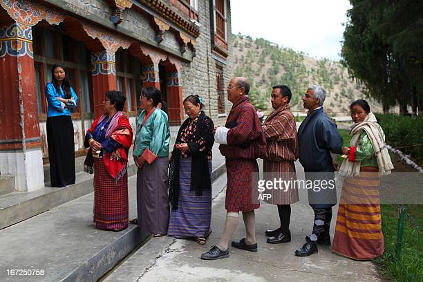 Residents queue as they wait to cast their votes at a polling station in Thimphu on April 23 during the second parliamentary elections of Bhutan The...