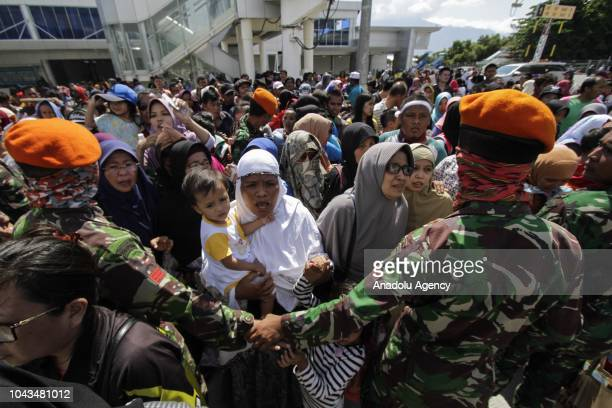 Residents queue to board a Hercules aircraft belonging to the Indonesian Air Force as they are being evacuated after the earthquake and tsunami that...