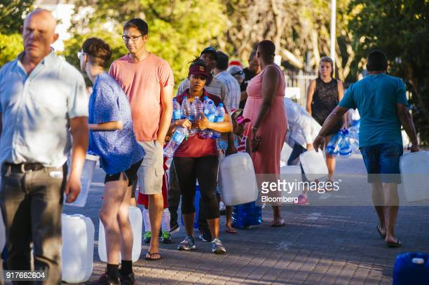 Residents queue to fill plastic water bottles and containers at a natural water spring on the site of SABMiller Plc's Newlands brewery in Cape Town...