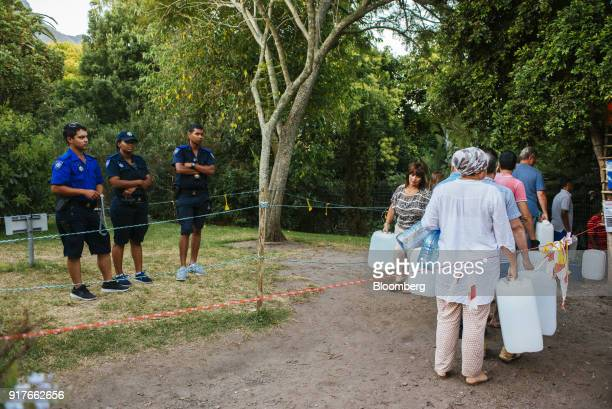 Residents queue to fill water bottles and containers as law enforcement officers stand guard at the Newlands natural water spring in Cape Town South...