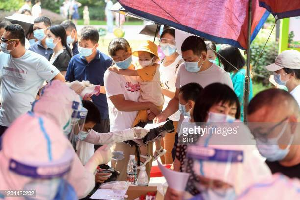 Residents queue to take nucleic acid tests for the coronavirus in Wuhan in China's central Hubei province on August 3 as the city tests its entire...