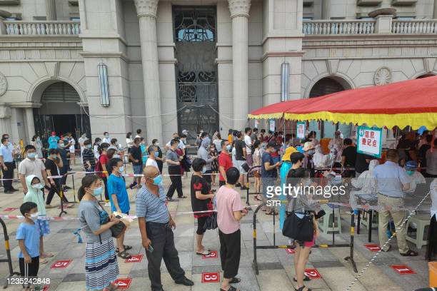 Residents queue to undergo nucleic acid tests for the Covid-19 coronavirus in Xiamen, in China's eastern Fujian province on September 14, 2021. -...