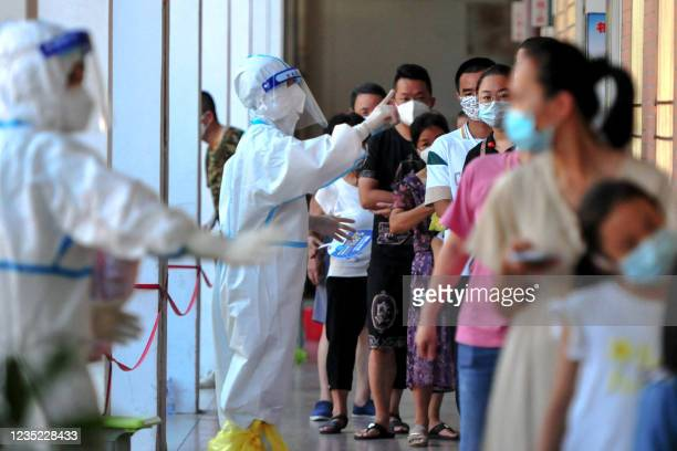 Residents queue to undergo nucleic acid tests for the Covid-19 coronavirus in Xianyou county, Putian city, in China's eastern Fujian province on...