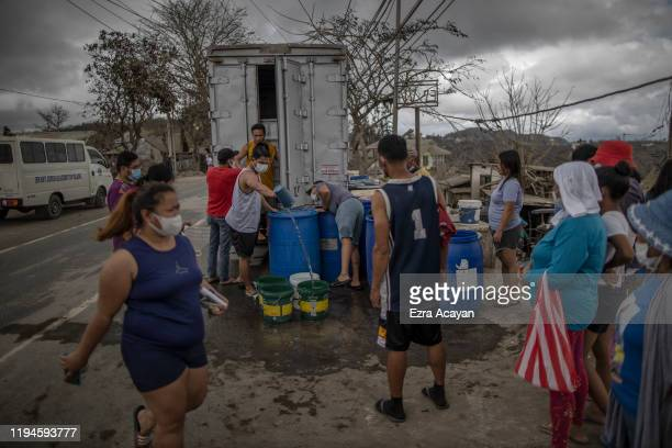 Residents queue up along a highway to receive water and relief goods on January 19 2020 in the outskirts of Tagaytay city Cavite province Philippines...