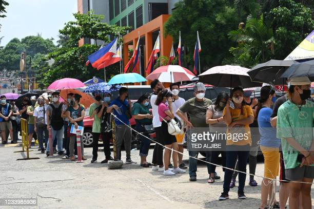 Residents queue up at a Covid-19 coronavirus vaccination centre in Mandaluyong City, suburban Manila on July 15, 2021.