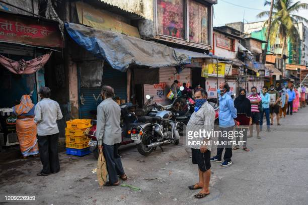 Residents queue up to collect milk inside the Dharavi slum during a governmentimposed nationwide lockdown as a preventive measure against the spread...