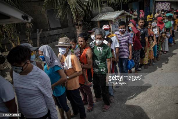 Residents queue up to receive relief goods on January 19 2020 in the village of San Guillermo Talisay Batangas province Philippines The Philippine...