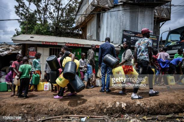 TOPSHOT Residents queue with their jerrycan to fill them with free water distributed by the Kenyan government at Kibera slum in Nairobi Kenya on...