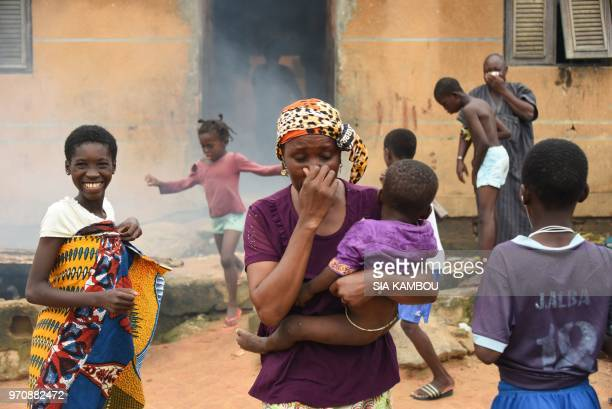 Residents react as agents of the National Institute of Public Hygene carry out fumigation in the Anyama district of Abidjan on June 9 as part of the...
