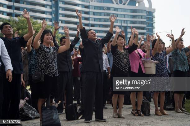 Residents react as they watch the televised annoucement on a big video screen on Mirae Scientists Street in Pyongyang that the country has...