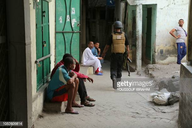 Residents reacts as a member of the Comoros Armed forces takes part in a search and patrol of Medina for weapons and armed men at Mutsamudu on...