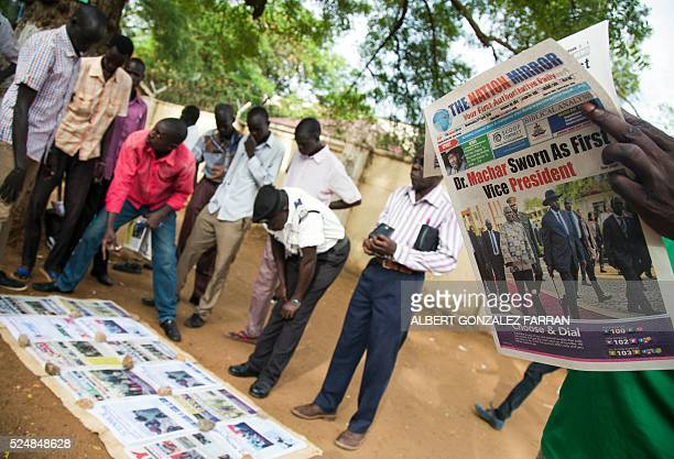 Residents read daily newspapers on April 27, 2016 reporting the arrival and sworning of rebel leader Riek Machar in Juba, South Sudan, a day after...