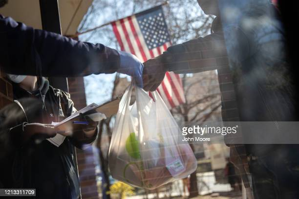 residents receive bags of free food at the WestCop community center on March 18 2020 in New Rochelle New York US National Guard troops are assisting...