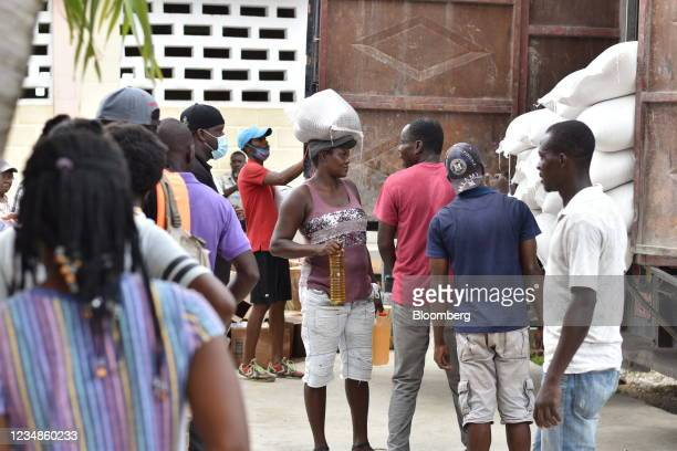 Residents receive bags of rice and cooking oil at a World Food Programme distribution site in Port-Salut, Haiti, on Tuesday, Aug. 24, 2021. Haiti's...