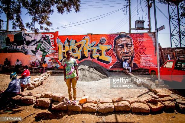 Residents relax in front of a painted wall with an Artwork mural of George floyd a black man who was killed by a policeman in Minneapolis