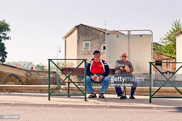 residents relaxing on public bench - bedarrides photos et images de collection