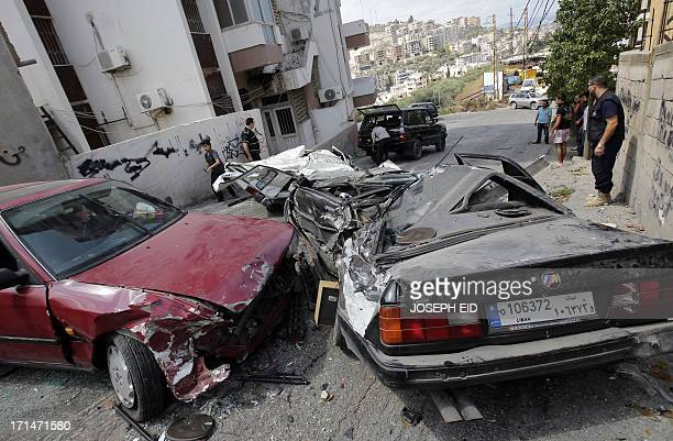 Residents remove crushed cars as they return to their homes near near the Bilal bin Rabah mosque in the Abra district of the southern city of Sidon...
