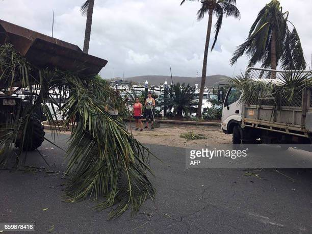 Residents remove fallen tree branches from the roads on Hamilton Island after strong Cyclone Debbie hit the Whitsundays Islands in Queensland on...