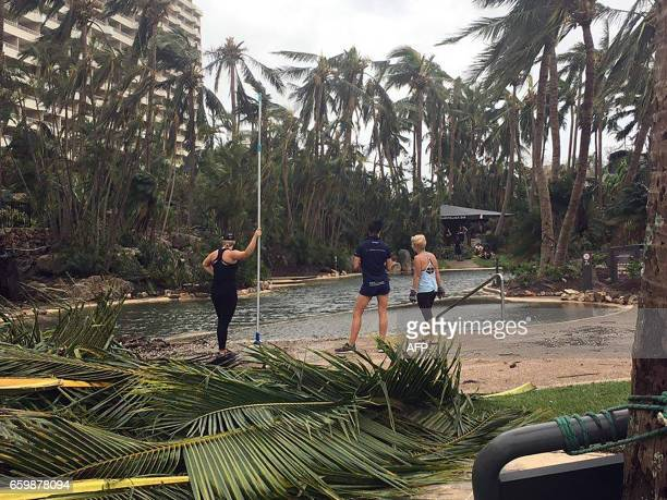 Residents remove fallen trees and branches from the roads on Hamilton Island after strong Cyclone Debbie hit the Whitsundays Islands in Queensland on...