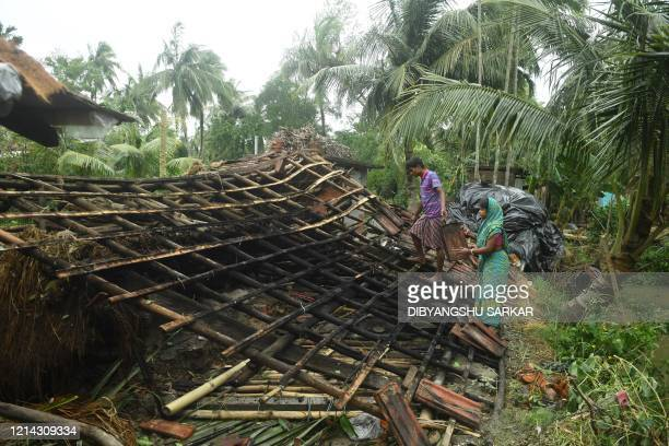 Residents repair the damaged roof of their house following the landfall of cyclone Amphan in Khejuri area of Midnapore West Bengal on May 21 2020 At...