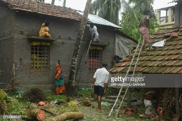 Residents repair the damaged roof of their houses following the landfall of cyclone Amphan in Khejuri area of Midnapore West Bengal on May 21 2020 At...