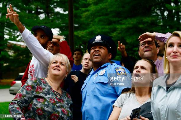 Residents reporters and police officers attempt to get a peak after someone believed to have seen a black bear in a tree which was reported roaming...