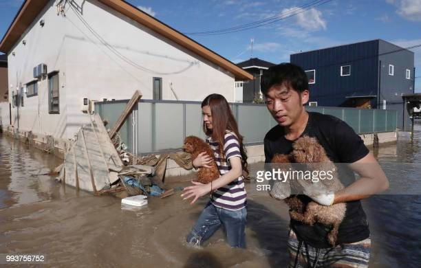 TOPSHOT Residents rescue dogs from flooded area in Kurashiki Okayama prefecture on July 8 2018 The death toll from record rains that have devastated...