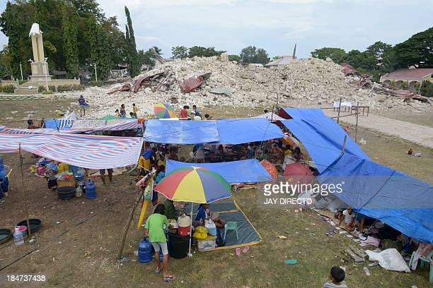 Residents rest at a temporary camp infront of the ruins of the 180 years old Our lady of light Church on the popular tourist island of Bohol central...
