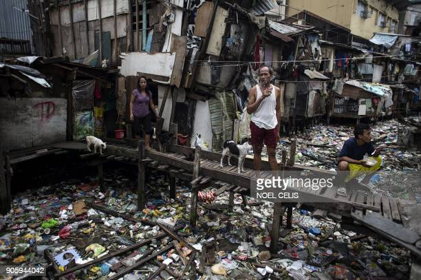 TOPSHOT Residents rest on a wooden bridge over a garbagefilled waterway in Manila on January 17 2018 / AFP PHOTO / NOEL CELIS