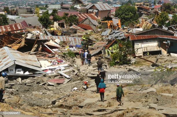 TOPSHOT Residents return to their collapsed homes to salvage belongings in Palu Indonesia's Central Sulawesi on October 1 after an earthquake and...