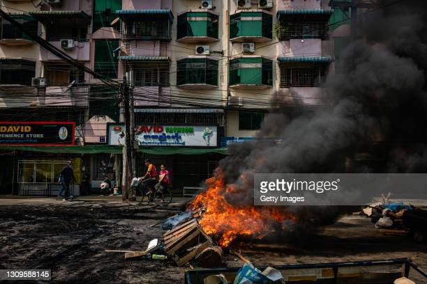 Residents ride a bicycle past tires set alight by anti-coup protesters at a blockade on March 28, 2021 in Yangon, Myanmar. Myanmar's military Junta...