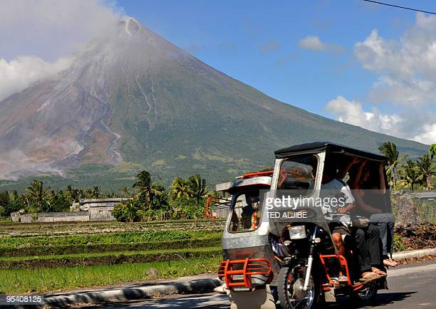 Residents ride a tricycle past the Mayon volcano in the city of Legazpi in Albay province 330 kms southeast of Manila on December 27 2009 The...