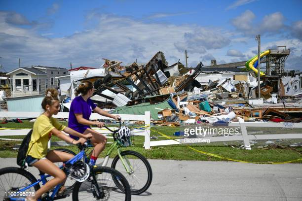 Residents ride bicycles past destroyed mobile homes in the Emerald Isle RV Park after a tornado touched down during Hurricane Dorian in Emerald Isle,...