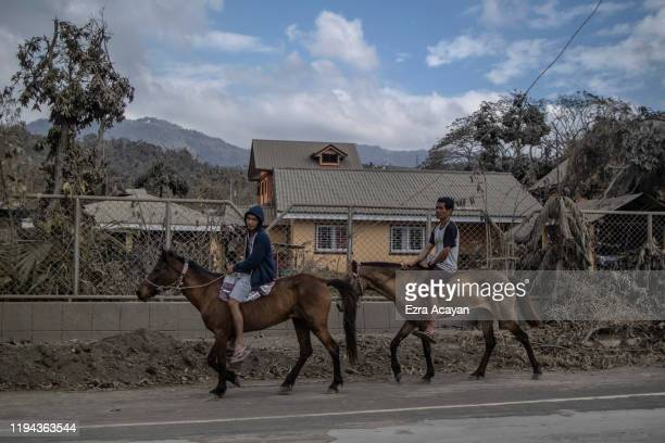 Residents ride horses along a highway covered in volcanic ash from Taal Volcano's eruption on January 18 2020 in Talisay Batangas province...